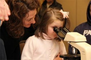 Child looking through microscope.