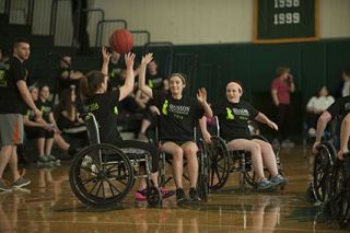 Students participating in wheelchair basketball event.