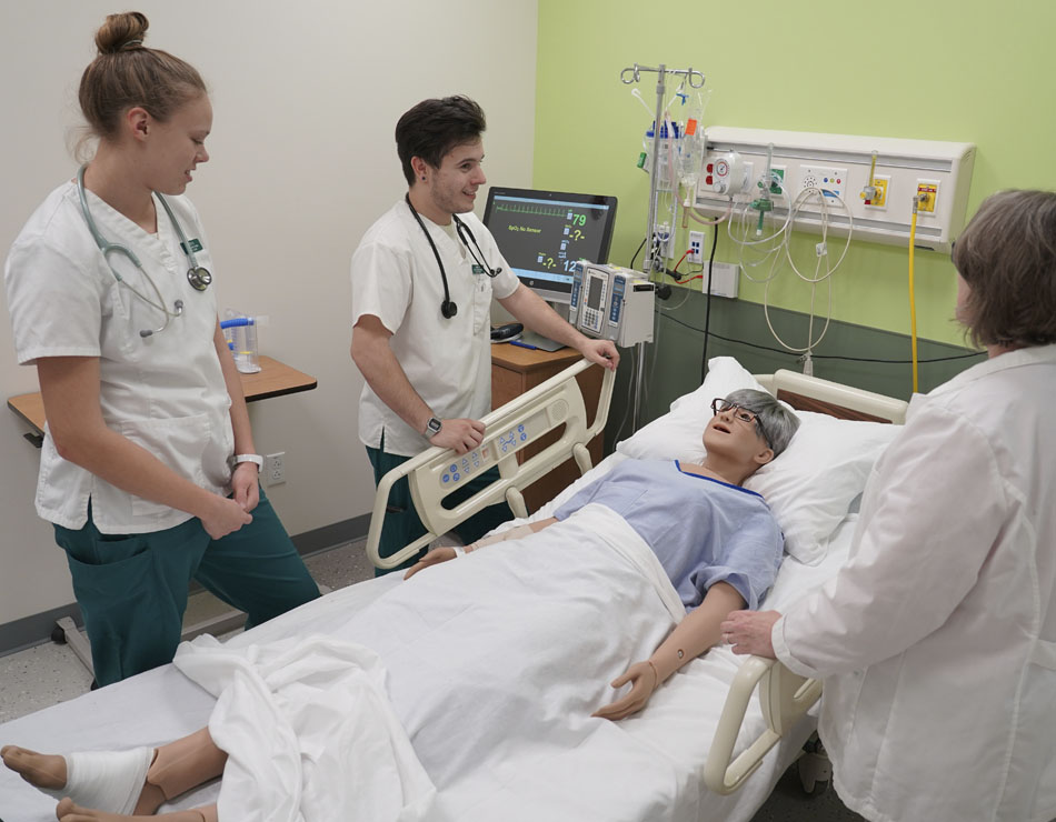 students work in a sim lab with faculty in the school of nursing