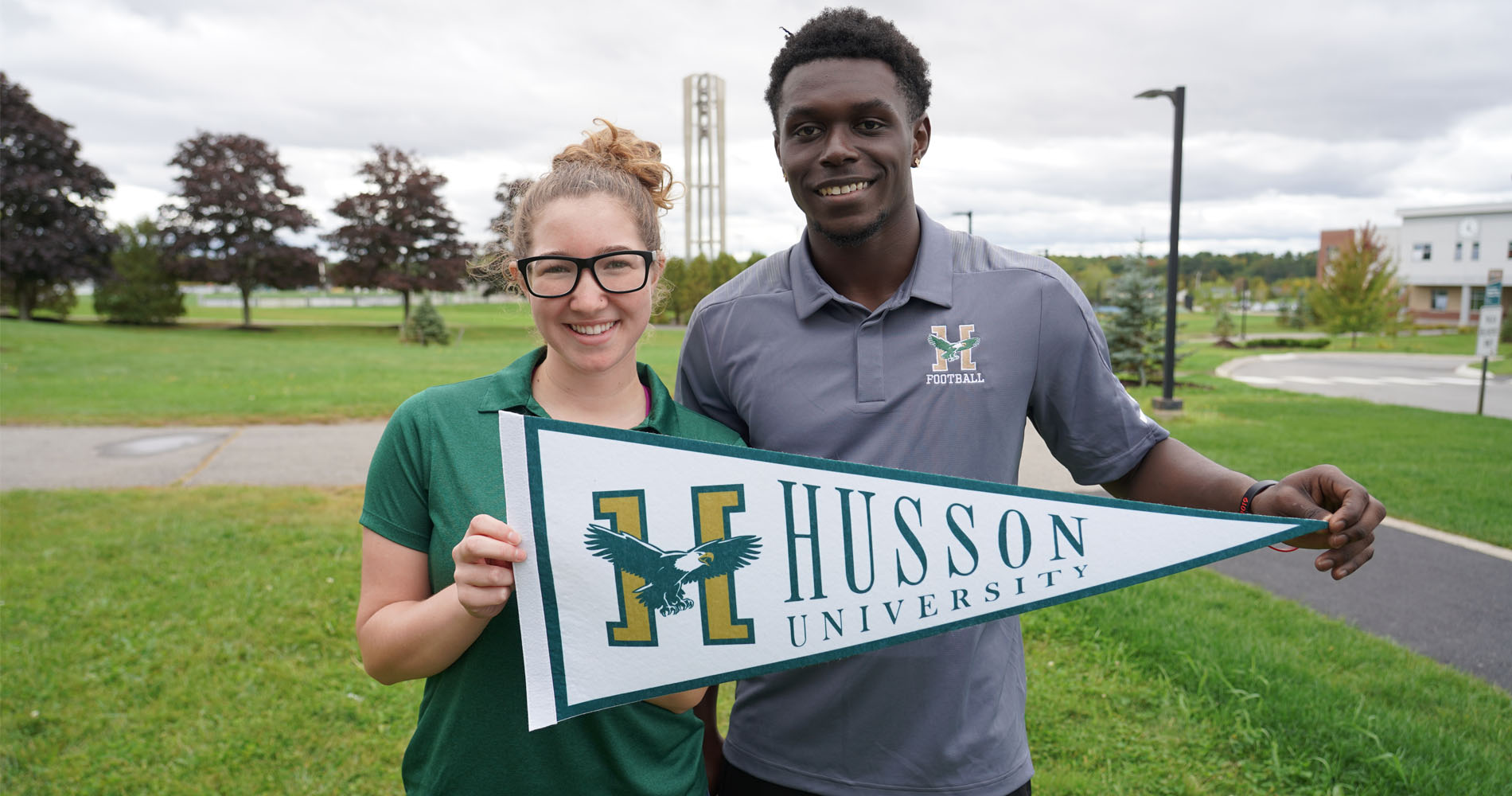 Students hold a pennant on the campus of Husson University