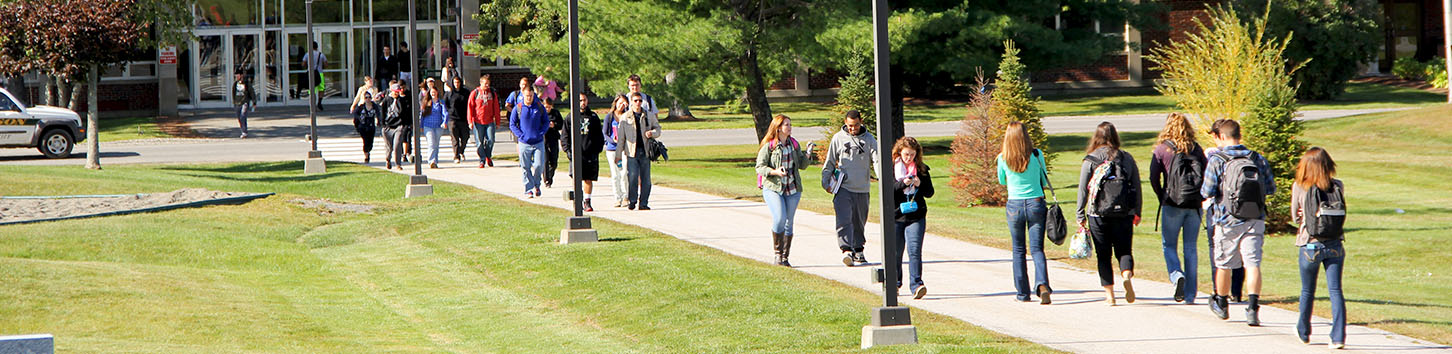 Student walking in on the campus of Husson University