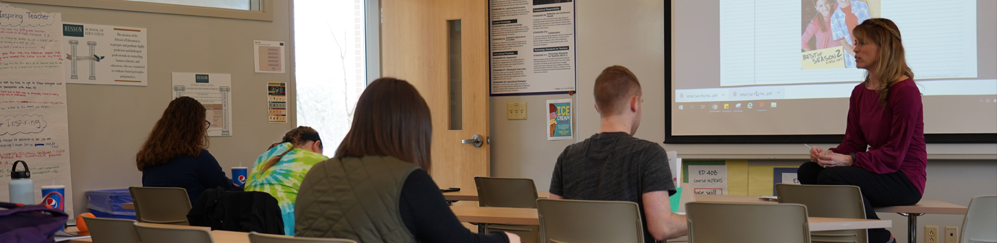 Students listen to faculty in a school of education class