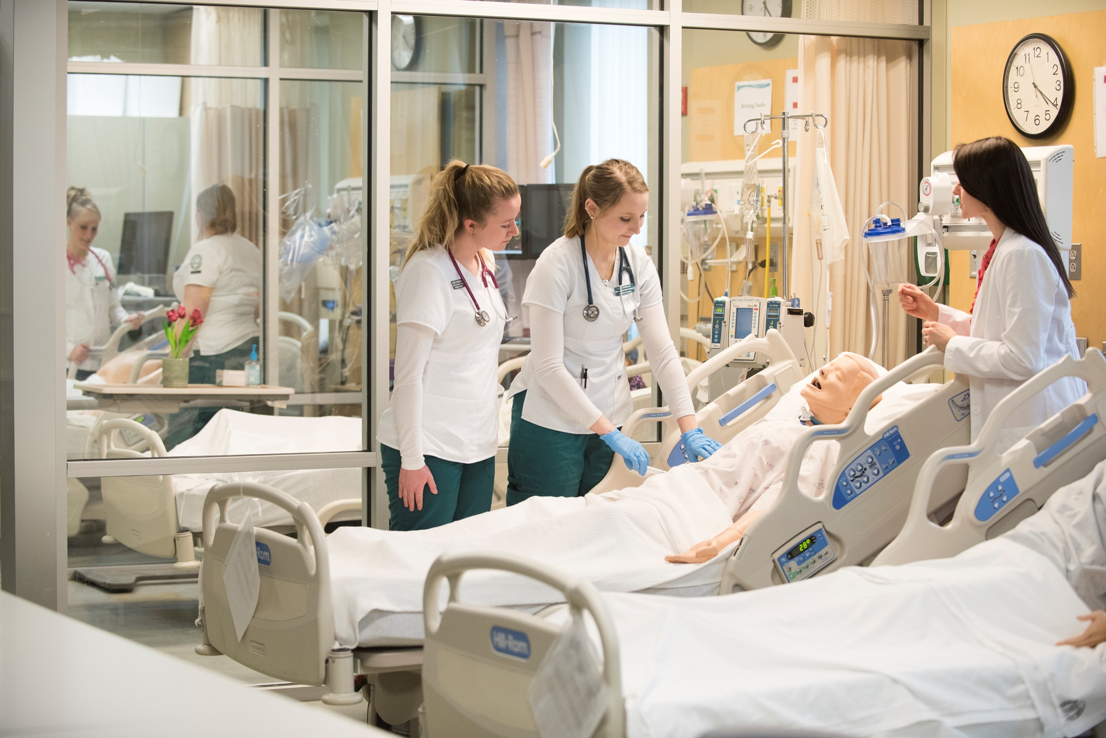 Students working in Nursing Simulation lab with staff