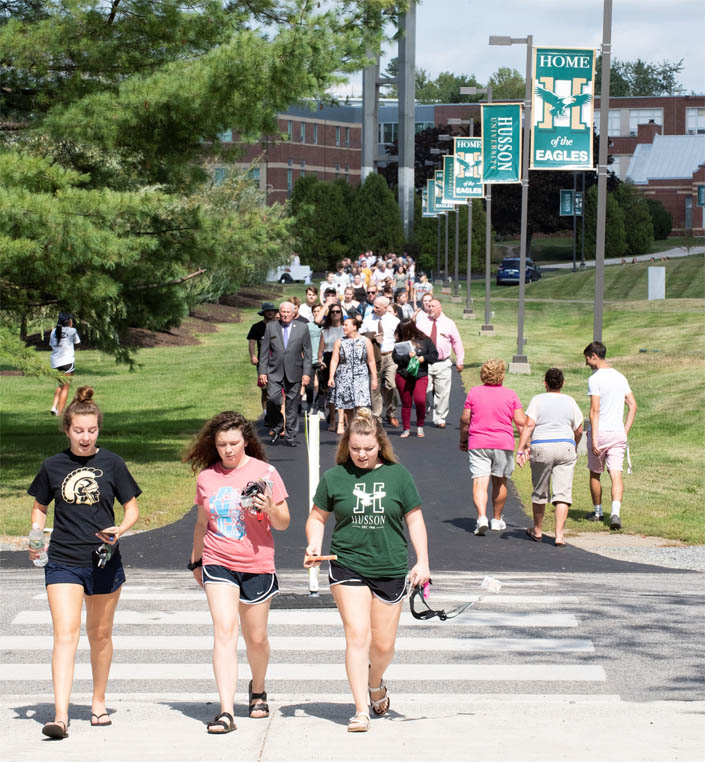 Students walk to convocation on the campus of Husson University