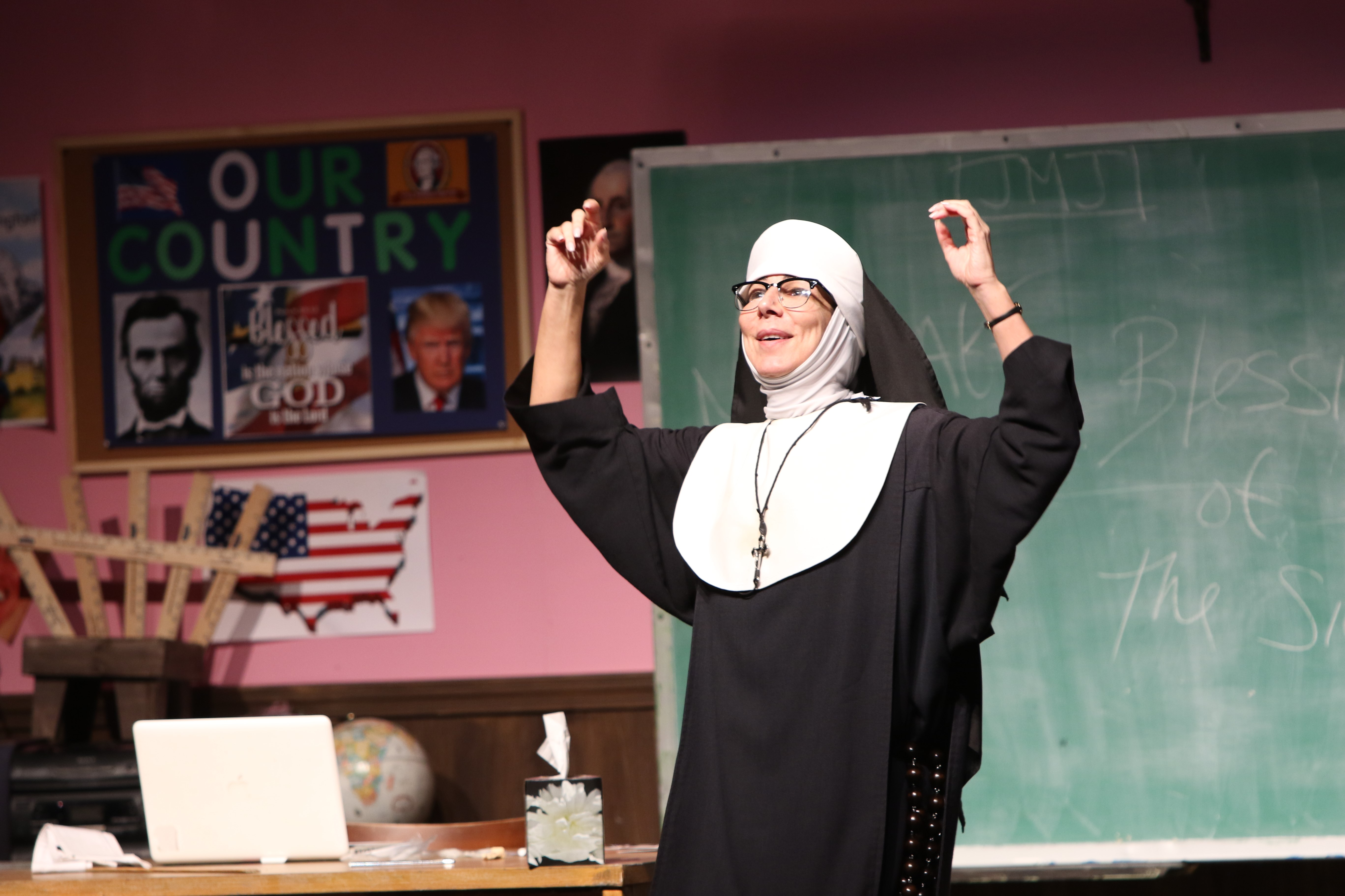 Nun dressed in a habit raises her arms